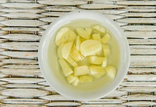В небольшую ёмкость налить немного масла, положить туда измельчённый чеснок